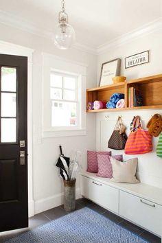 Hall d'entrée cosy avec coussins, banc, rangements, crochets pour les sacs à mains, sceau à parapluies, étagères et tapis