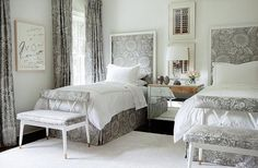 Gray shared bedroom features a pair of gray print headboard in Brunschwig & Fils Soleil Silk Wrap Print Fabric trimmed with white borders on twin beds dressed in white and gray hotel bedding flanking a 3 drawer mirrored footed nightstand.