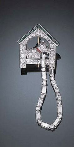AN ART DECO DIAMOND, EMERALD AND RUBY DOG HOUSE BROOCH Designed as a pavé-set diamond dog to the circular-cut emerald eye and baguette-cut ruby collar to the baguette-cut diamond leash, mounted in platinum, circa 1925.