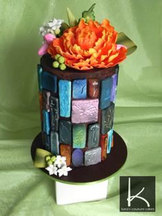 Spring, Stones, and Chocolate Ganache -  double barrel cake was a 6 inch round standing 8.5 inches high. Its covered in dark chocolate ganache and imprinted modeling chocolate stones as well as a sugar flower spray.
