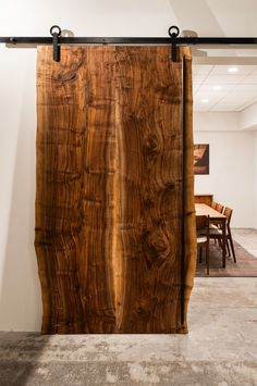 Out Baldur sliding door hardware in Black Stainless is the perfect companion for this beautiful live-edge door panel in the Joinery's new downtown showroom.