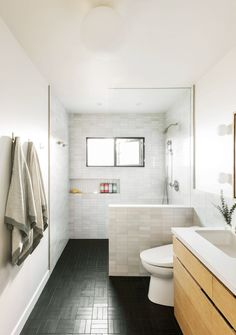 Barnoon opted for mixed, light gray tile from Heath Ceramics on the shower and backsplash, and black Heath field tile on the floor.