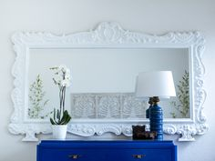 An old fleamarket mirror gets painted white to match the walls and now makes a bold statement in the master bedroom