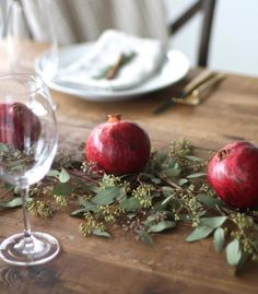 déco table de Noël naturelle - grenades et feuilles vertes sur la table en bois