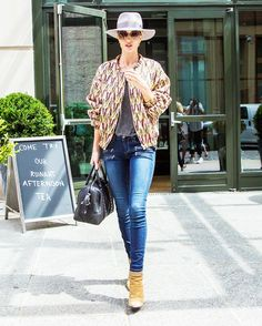 Rosie Huntington-Whiteley wears an Isabel Marant printed jacket, t-shirt, Paige jeans, Maison Michel hat, Chloé sunglasses, Givenchy bag, and Saint Laurent boots