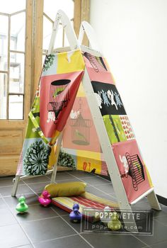 Cover a wooden ladder with funky fabric  create a perfect play tent.