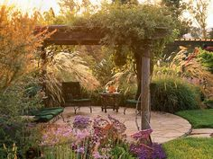 Rustic Retreat ~ This rickety old arbor in an unimproved area of this garden seemed an unlikely place for an intimate outdoor room. It was shorter than normal--about 7 feet tall instead of the typical 8 feet or taller. Nevertheless, it became an informal retreat. The patio beneath is paved with randomly cut flagstone that's mortared in place for easy maintenance. An unmortared flagstone path, designed to match the arbor's rustic style, leads to the patio.