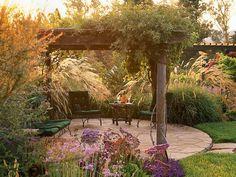 an arbor above a stone patio makes an outdoor room