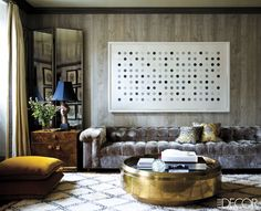 A Damien Hirst etching hangs above a Dunbar sofa in the library of Jackie Astier's Upper East Side Home. The artwork brings a sense of levity to the space without detracting from its polished style. Tour the rest of the home.   - ELLEDecor.com