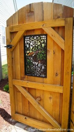 If you're looking to keep your garden or backyard relatively private but don't like the look of solid wood, try adding a peek-a-boo insert. Here, an intricate black Nuvo Iron decorative window insert adds a bit of flourish without sacrificing functionality. Click through for more garden gate ideas for decorating your backyard.