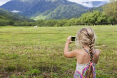 Caucasian girl taking photograph of rural meadow - stock photo