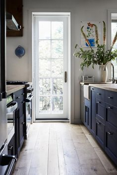 Blue galley kitchen with wood countertops.