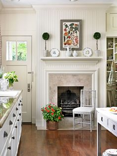 We love the fireplace in the kitchen, which is accessorized with small topiaries, a framed botanical, and English china - Traditional Home®  Photo: Emily Followill Design: Lillian August