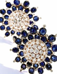 A Pair of 18 Karat Gold, Sapphire and Diamond Brooches, Van Cleef & Arpels – Designed as two flowerheads, the petals composed of round, oval and cushion-cut sapphires weighing approximately 20.00 carats, accented by numerous round and cushion-cut diamonds weighing approximately 9.80 carats