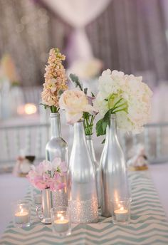 Bottles, silver paint, dust some glitter and some seasonal flowers and you have a wedding table centerpiece that will dazzle your guests! Silver Wedding Centerpieces, Wine Bottle Centerpieces, Silver Centerpiece, Wedding Reception Decorations, Flower Centerpieces, Wedding Themes, Diy Wedding, Rustic Wedding, Wedding Flowers