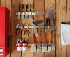 These metal strips are knife magnets, usually used in kitchens; here they hold tools and paintbrushes.