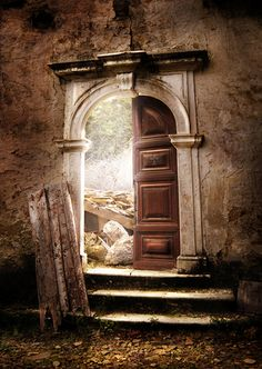 An open door leads out from the ruins of an abandoned monastery.  It almost looks like the doorway to Narnia or some other enchanted land. Mesmerizing photograph!