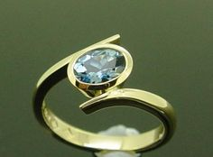 Lovely Aquamarine Dress Ring with soft flowing curves sweeping the Aquamarine bezel set in 18 carat Yellow Gold. Aquamarine is the birthstone for March.