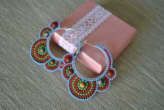 These multicolored seed beaded hoops are created using blue, red, green, golden brown seed beads and picasso jasper stone beads. Measurements : interior hoop diameter is 3 cm, 5,5 cm wide and 6 cm long These earrings would be great to create a unique look for yourself or