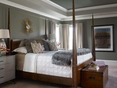 A tray ceiling painted with light and dark shades of gray and trimmed in white creates dimension over this stylish bedroom design. A wooden bed frame features tall pyramid posts, and the bed linens combine a traditional white cover with a faux fur accent throw and decorative pillows. A metallic sunburst draws light to the wall to finish the look.