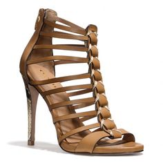 The Josey Heel from Coach - A stiletto heel wrapped in python-printed leather adds an exotic accent to this dramatic cage sandal. Crafted in vegetable-tanned leather with leather soles, the design is finished with an edgy exposed zipper at the back edge.