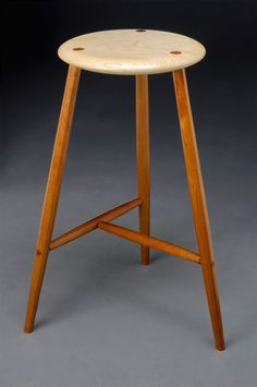 Three legged stool with faceted Paduk legs and sugar Maple seat.