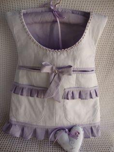 Vestido porta - fraldas ou porta - trecos, todo em matelassê, estruturado com manta acrílica, medindo 35 largura x 40 altura, podendo ter até 5 bolsos ( um grande no decote, dois bolsos embutidos e um ou dois bolsos com babadinhos). <br>Acompanha cabide forrado e sachê coração com inicial do bebê bordado. <br>Pode ser usado para colocar fraldas, acessórios do bebê, kit higiene, brinquedinhos. <br>Feito em tecido de algodão 100% e pré - lavado. <br>Feito sob encomenda, nas cores de sua…