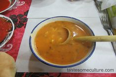 A bowl of Moroccan harira soup with a wooden spoon and a strong orange color showing the flavor of the soup.