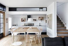 Open-plan kitchen/dining: dining table that doubles as bench space, white drum-shade arced floor lamp, white wooden wall panelling, lowered mezzanine with skylight