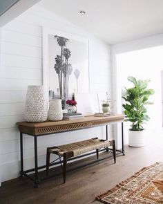 Modern Coastal Beach House Decor In An Entryway Featuring A Rustic Table And Woven Bench Large Blackened White Palm Tree Artwork Clay Pots