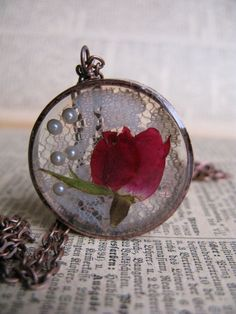 real rosebud flower & lace encased in resin with open back copper bezel.