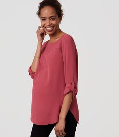 Pretty up your style routine with this flowy shirred blouse, detailed with ruffled shoulders. Round neck. Long sleeves with button cuffs. Ruffled shoulders. Shirred beneath front and back yoke. Back button keyhole. Shirttail hem.