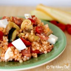 Pearl couscous with salami, roasted vegetables, artichoke hearts, and mozzarella, all tossed with a tomato vinaigrette.