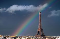 """A rainbow arcs across the sky, framing the world famous Eiffel Tower in Paris. Keen-eyed photographer and concert violinist Bertrand Kulik captured the picturesque scene from his flat's window. He said: """"I was at home giving a violin lesson to a student when I saw out of the corner of my eye the rainbow forming. I quickly opened my window, leaned out and took some pictures - all while the student was still playing."""""""