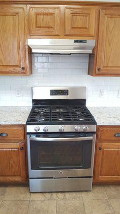 White subway tile, stainless appliances, honey-oak cabinets