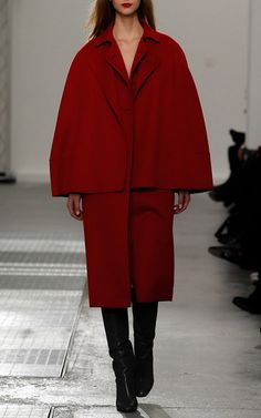 Rendered in wool, this **Agnona** coat features a pointed collar, double breasted button closures at the bodice, and the option to detach the cape.