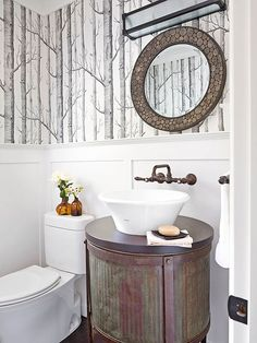 Industrial Flair - I LOVE THIS BATHROOM HAS THE VERTICAL TREES ON THE WALLPAPER AND THEN THE ROUND MIRROR, SINK AND GREAT VANITY.