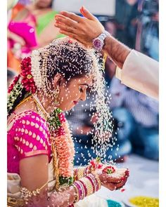 A South Indian bride is showered with rice during the wedding ceremony