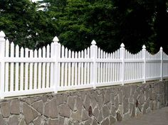 This vinyl picket fence has a bottom rail under the pickets.