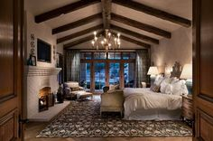 TV This gorgeous master bedroom has high ceiling with stunning rustic wood work. It's egg shell white old brick fireplace has a cozy television nestled into the wall above it.