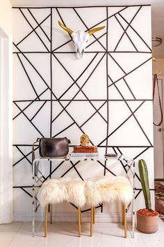 DIY accent wall, steer skull, sheepskin stools, and cactus