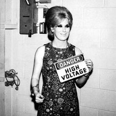 """Best known for her peroxide blonde beehive, hit tracks and soulful voice, Dusty Springfield is an icon of the 'Swinging 60s' and remains as a face of the era. Springfield in this black and white portrait is shown in 60's attire holding a small placard saying """"Danger"""""""