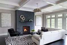 Semerjian Interiors - Modern Family Room with coffered ceiling, stone fireplace surround, zebra rug.