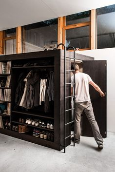 The living cube by Till Könneker is a minimalistic cube design with a shelf for vinyl collection, TV, clothes and shoes. On the cube is a guest bed and inside the cube is a lot of storage space.