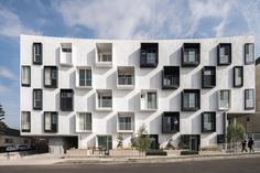 American firm Lorcan O'Herlihy Architects has completed a multifamily apartment building with a sculptural interior courtyard and a monochrome facade.