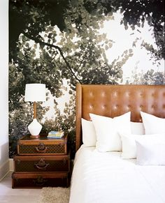 Treetops wallpaper in masculine bedroom with leather headboard