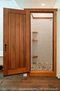 custom wood door for shower. wood corner shelves. Shower floor uses rocks we gathered from the beach