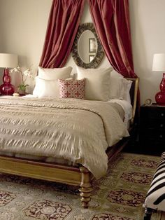 Neutral fabrics and finishes, with a red cherry on top in the form of lamps and a cranberry silk swag. Buy pre-made curtains, hang them on a short rod and tuck them behind the headboard.  Zebra-print bench on the right introduces a bit of whimsy.