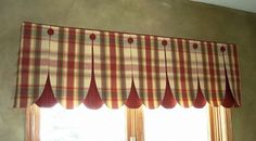 Petal valance made by overlapping two coordinating fabric flaps. There is piping along the top edge, as well as covered buttons.