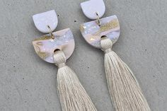 Tiered Tassel - Champagne Nude, cream and gold glitter polymer clay with cream tassel. Surgical steel ear posts with stainless steel extra secure rubber ear nuts. Measuring approximately 100mm long x 28mm wide. Very lightweight. Can be easily trimmed to shorter length. These